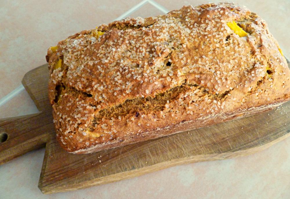 loaf of mango banana bread on cutting board
