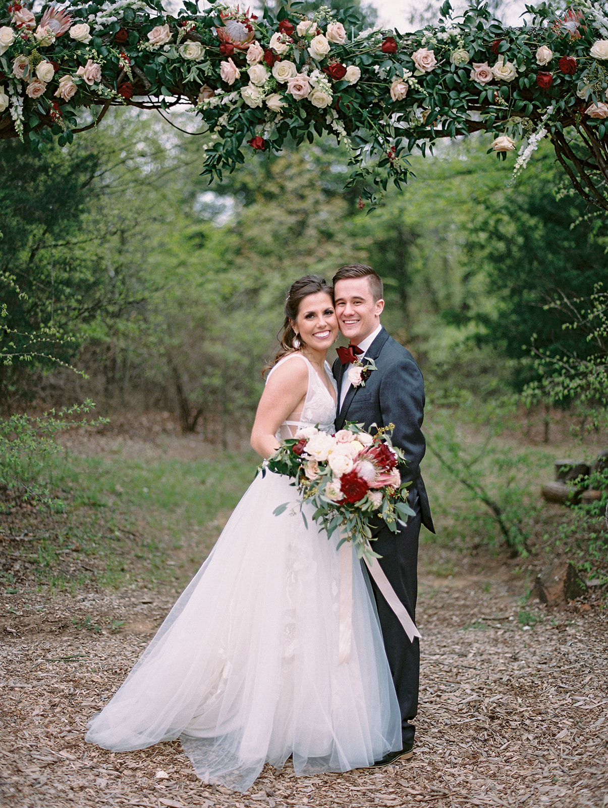 bride and groom under the floral arch