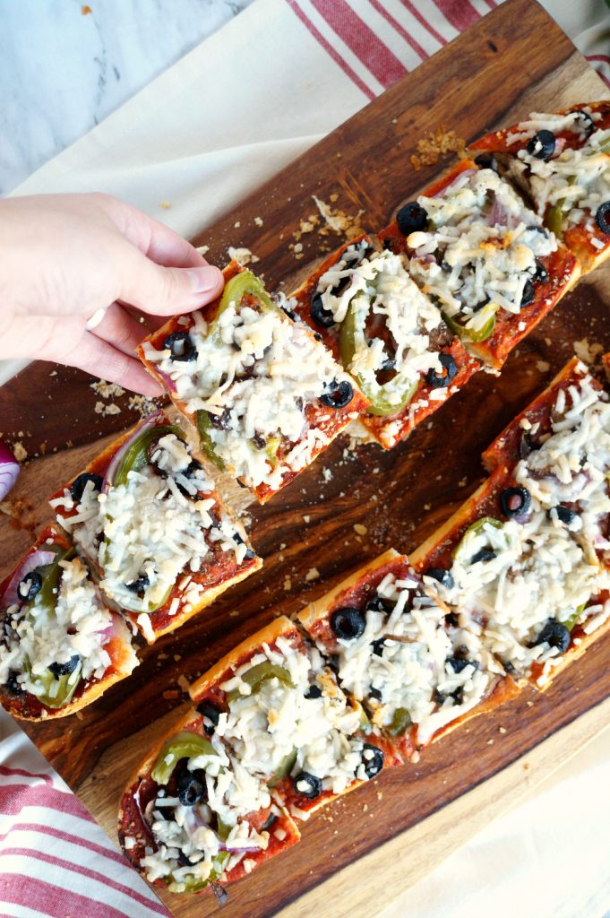 french bread pizza with someone grabbing a piece