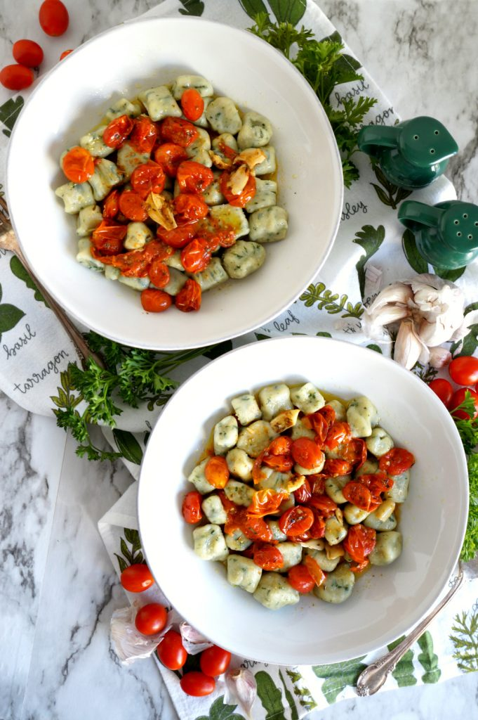 two plates of spinach gnocchi with tomato sauce