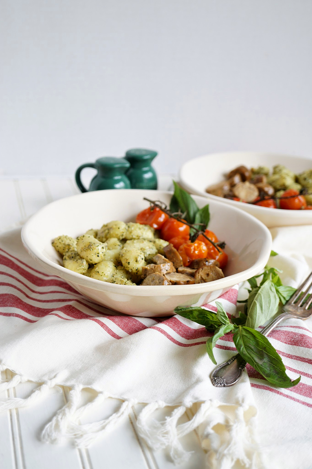 plate of gnocchi with pesto, sausage, and tomatoes