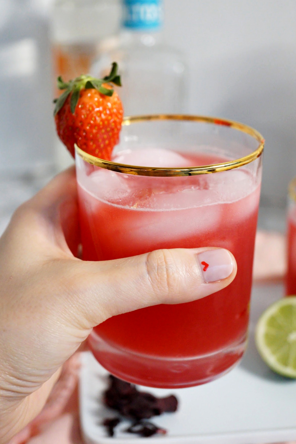 holding a glass of strawberry hibiscus margaritas