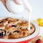 pouring glaze on lemon berry rolls