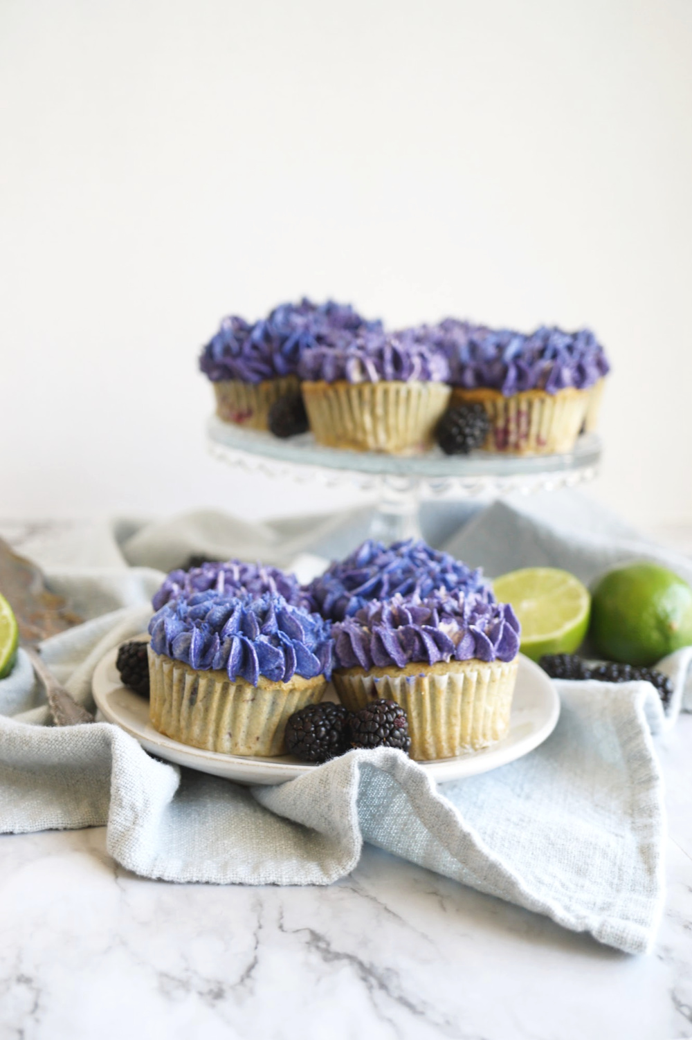 vegan blackberry lime cupcakes on a plate and on stand
