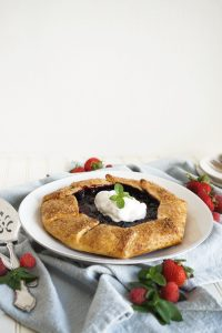 berry galette on plate with whipped cream on top
