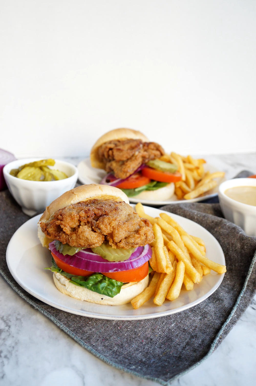 fried chick'n oyster mushroom sandwich on plate with fries
