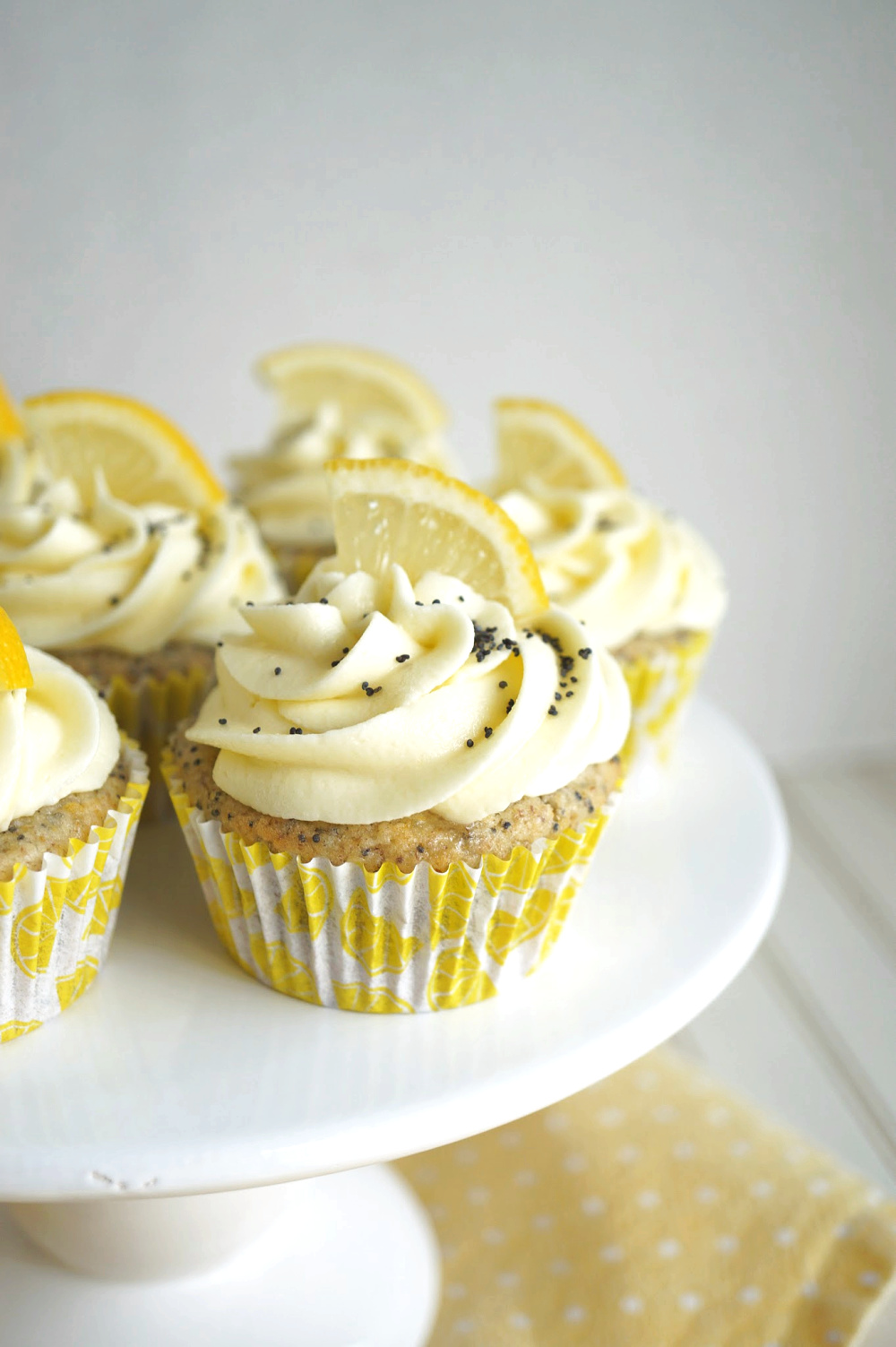lemon poppyseed cupcake on cake stand