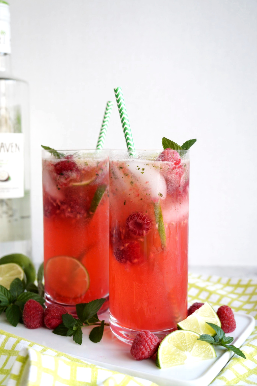 two glasses of raspberry coconut mojitos on tray