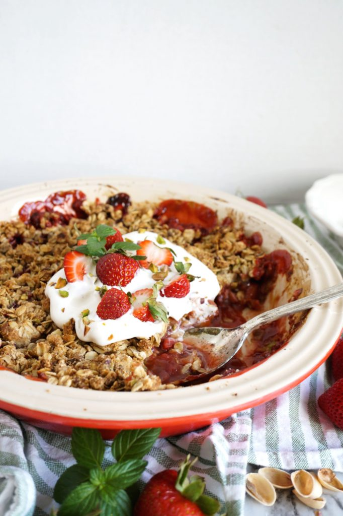 dish of strawberry pistachio crisp with serving spoon