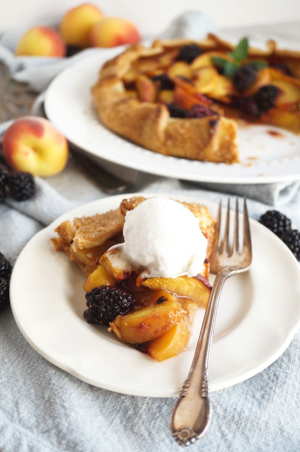 slice of blackberry peach galette on plate with ice cream
