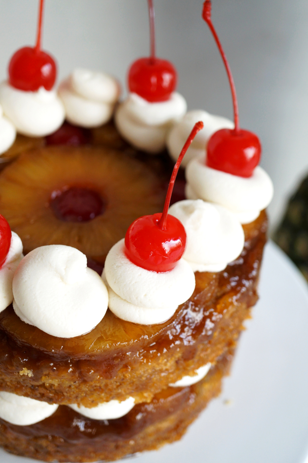 close up of cherries on top of pineapple cake