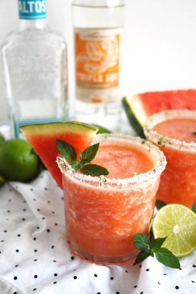 cup of watermelon mint frozen margarita with a wedge of watermelon