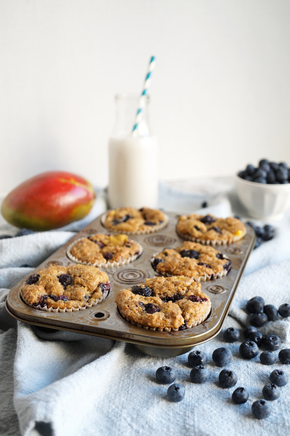 blueberry mango muffins in metal pan with fruits