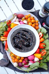 overhead shot of black lentil peppercorn hummus with colorful vegetables