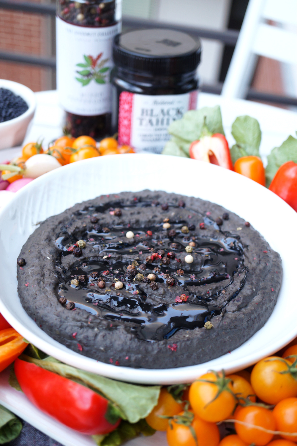 bowl of black lentil hummus with tahini drizzle and peppercorns