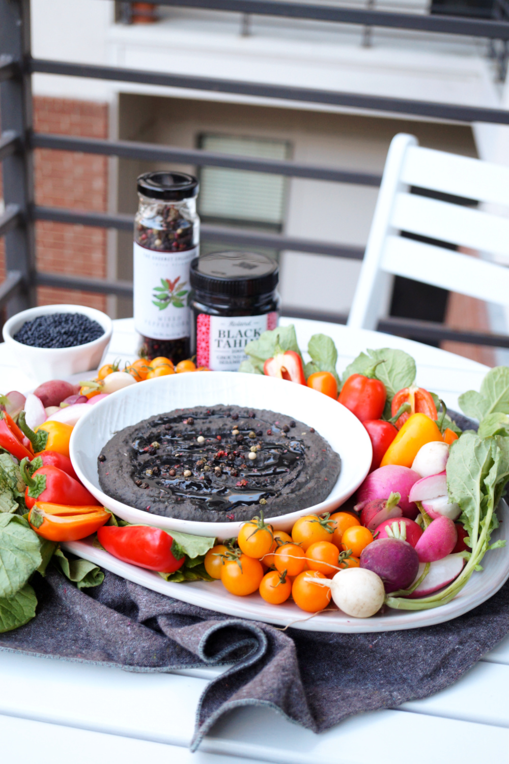 far away shot of black lentil hummus with colorful vegetables on a tray