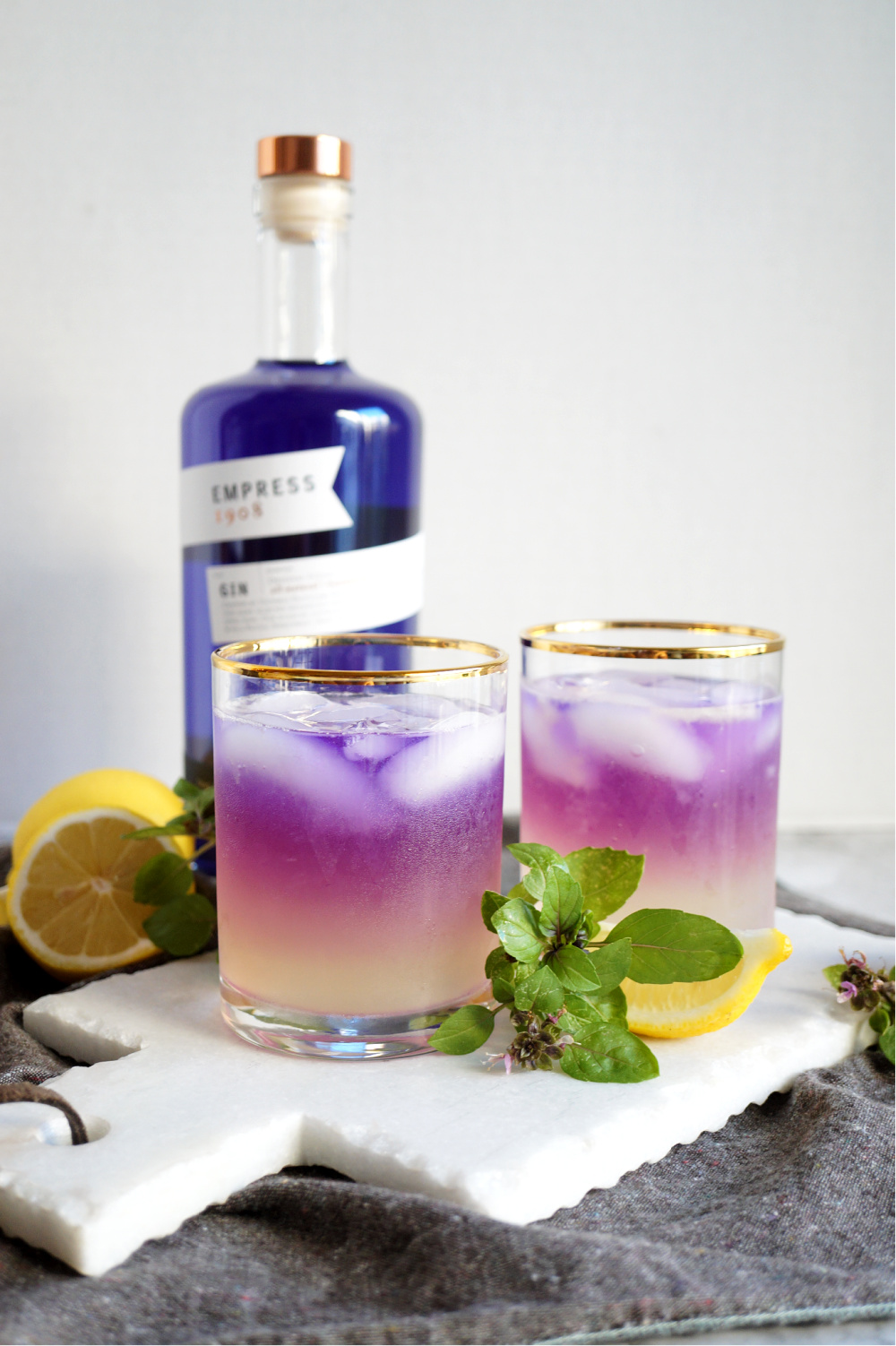 two glasses of purple basil gin fizz decorated with basil leaves and lemon slices