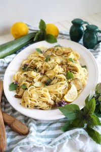 plate of pasta with zucchini, lemon slices and basil leaves