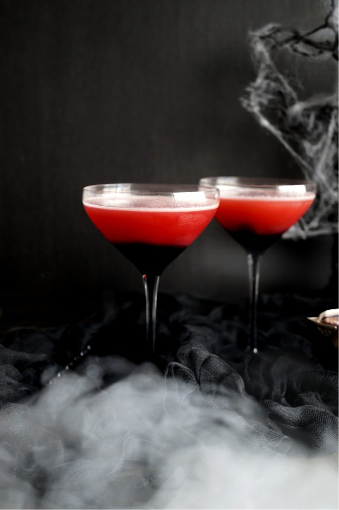 two glasses of red cocktail with spooky background and fog