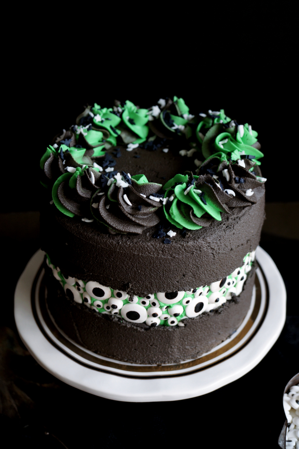 angled shot of black cake with candy eyeballs