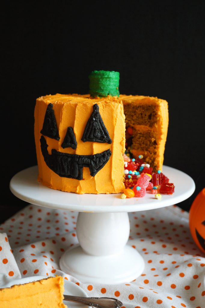 pumpkin cake with slice cut and candy pouring out
