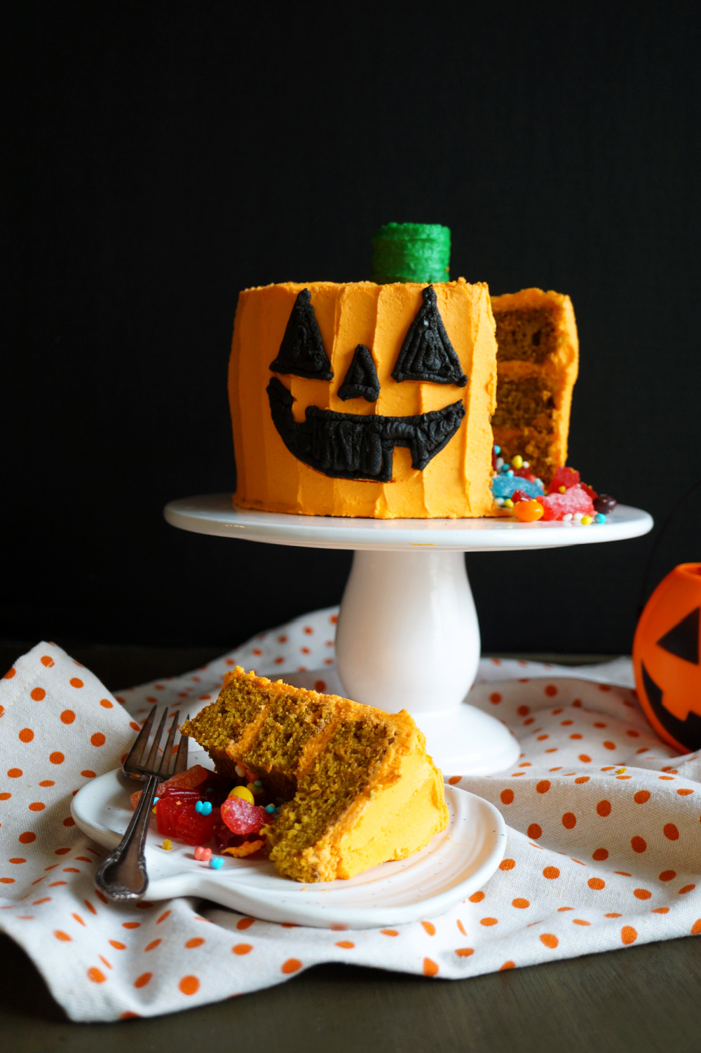 jack o'lantern cake with candy and slice on plate