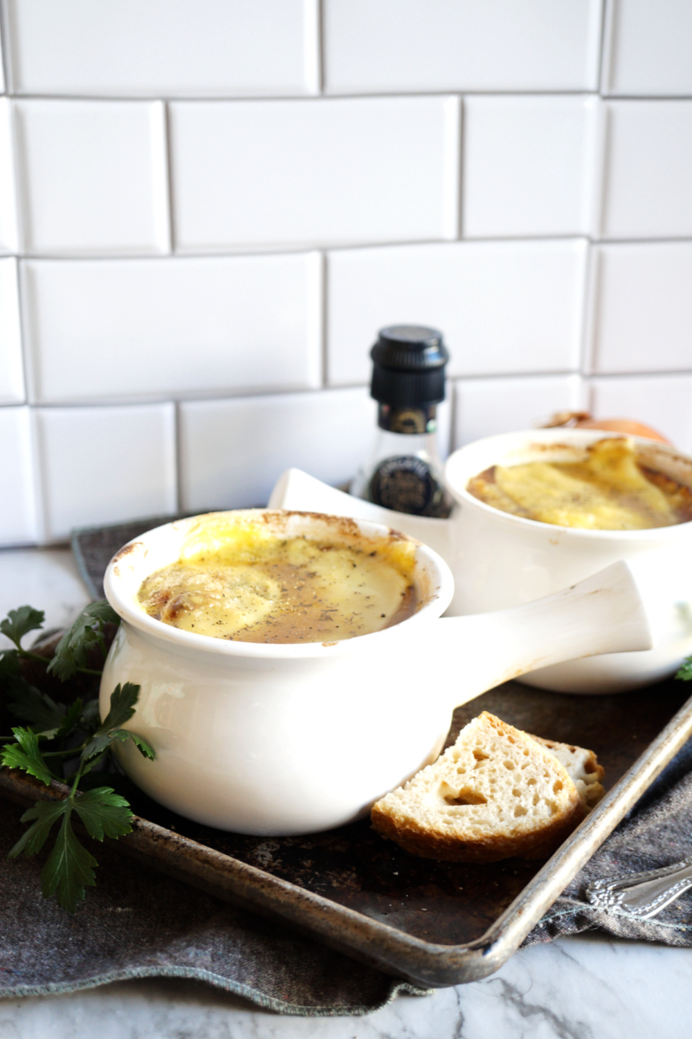 two bowls of french onion soup on pan