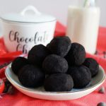 black cocoa truffles on white plate with red towel