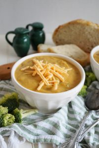 bowl of broccoli cheese soup with shredded cheese on top