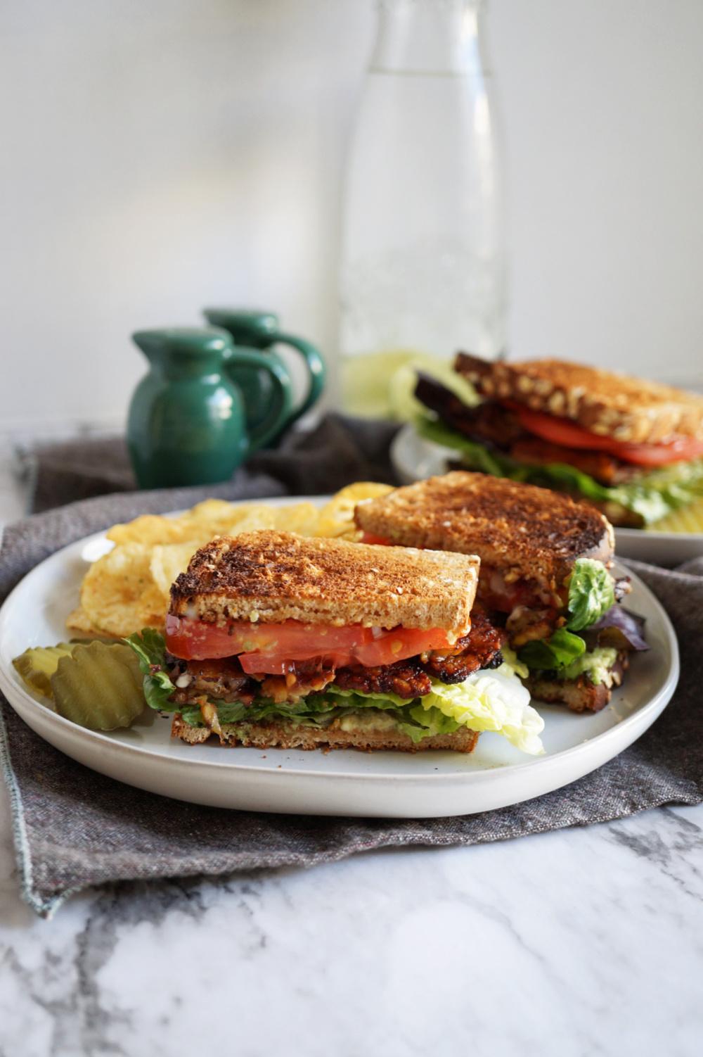 vegan BLT sandwich on a plate cut in half