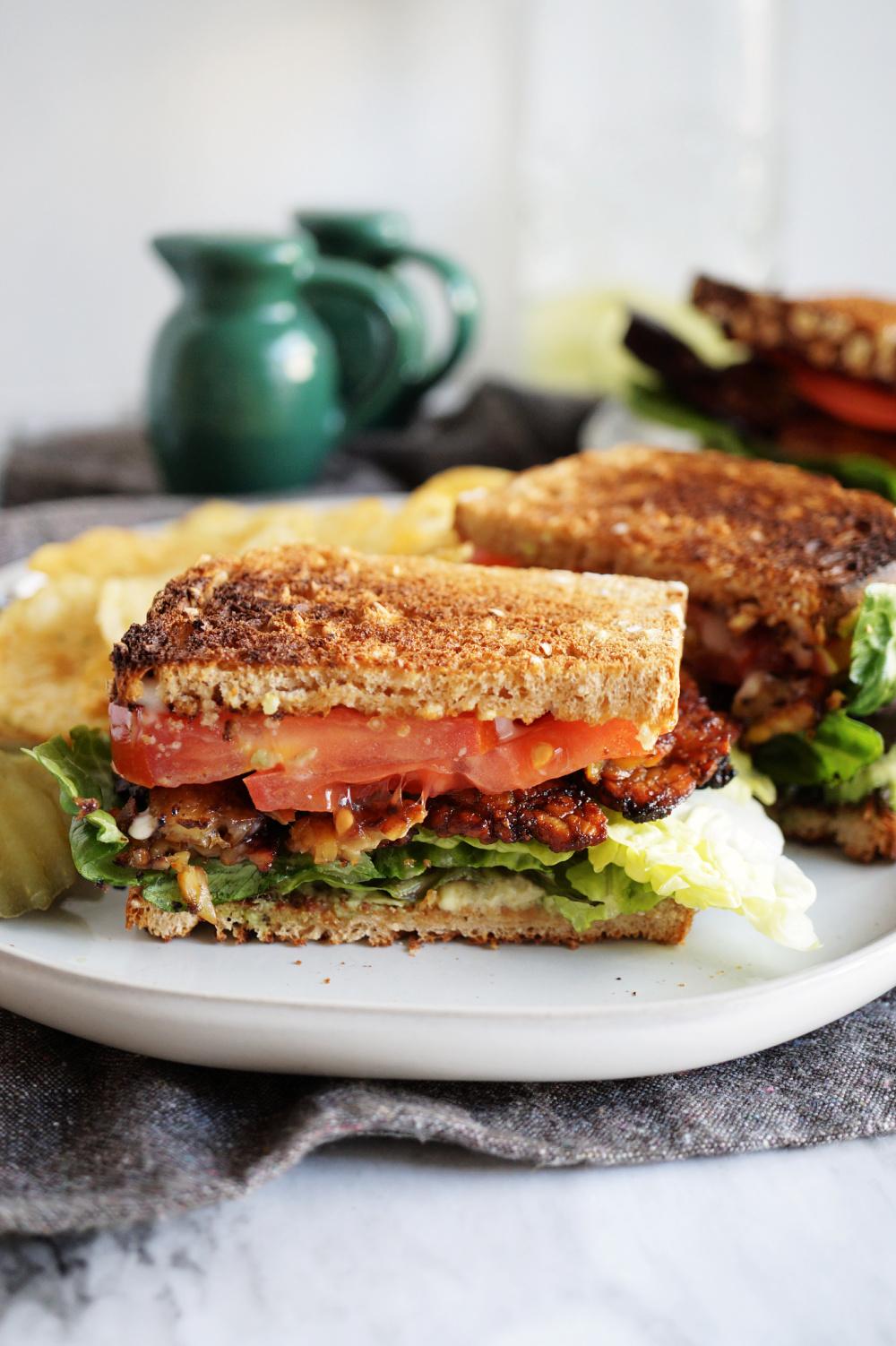 BLT sandwich cut in half on white plate