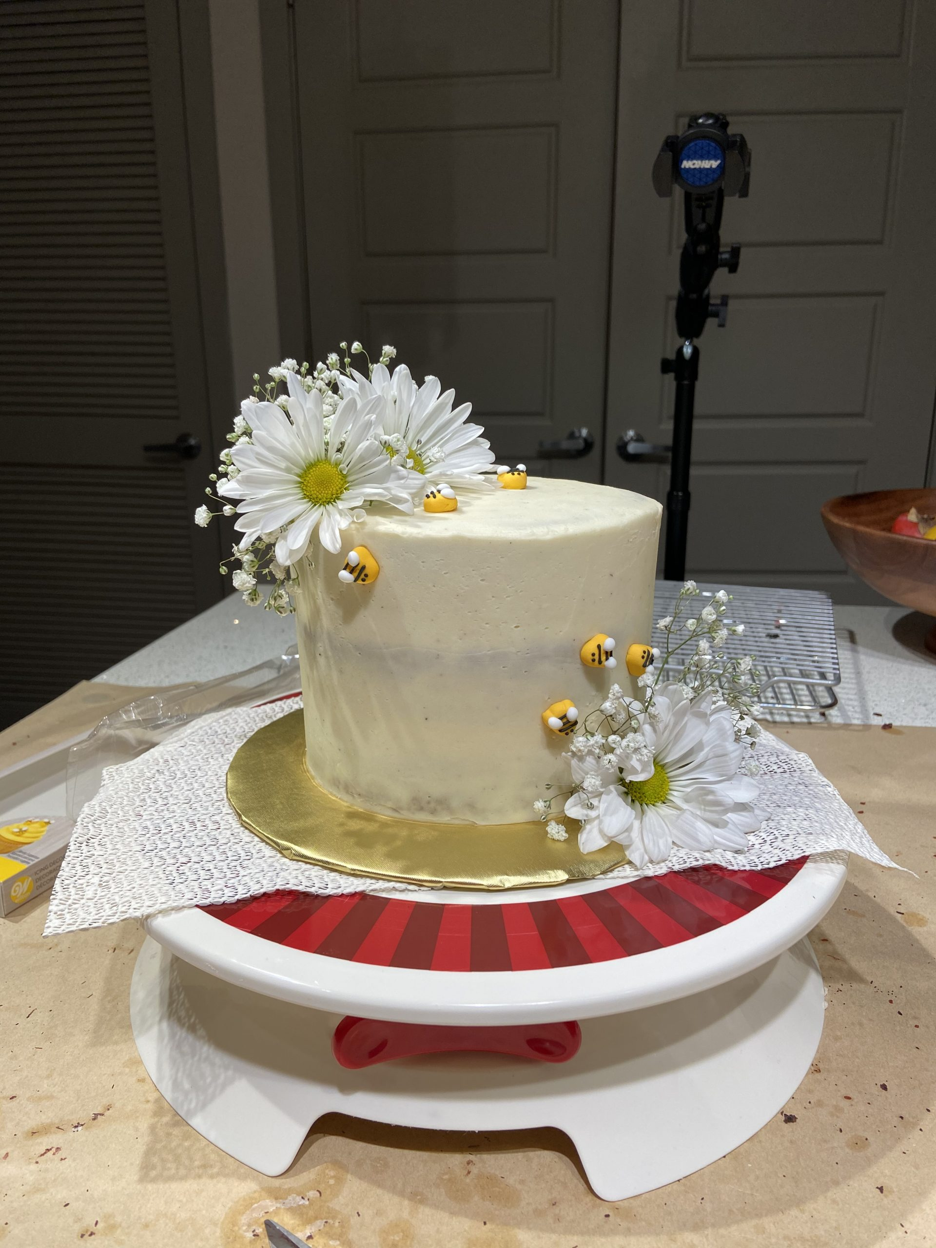 white cake with flowers and small icing bumblebees