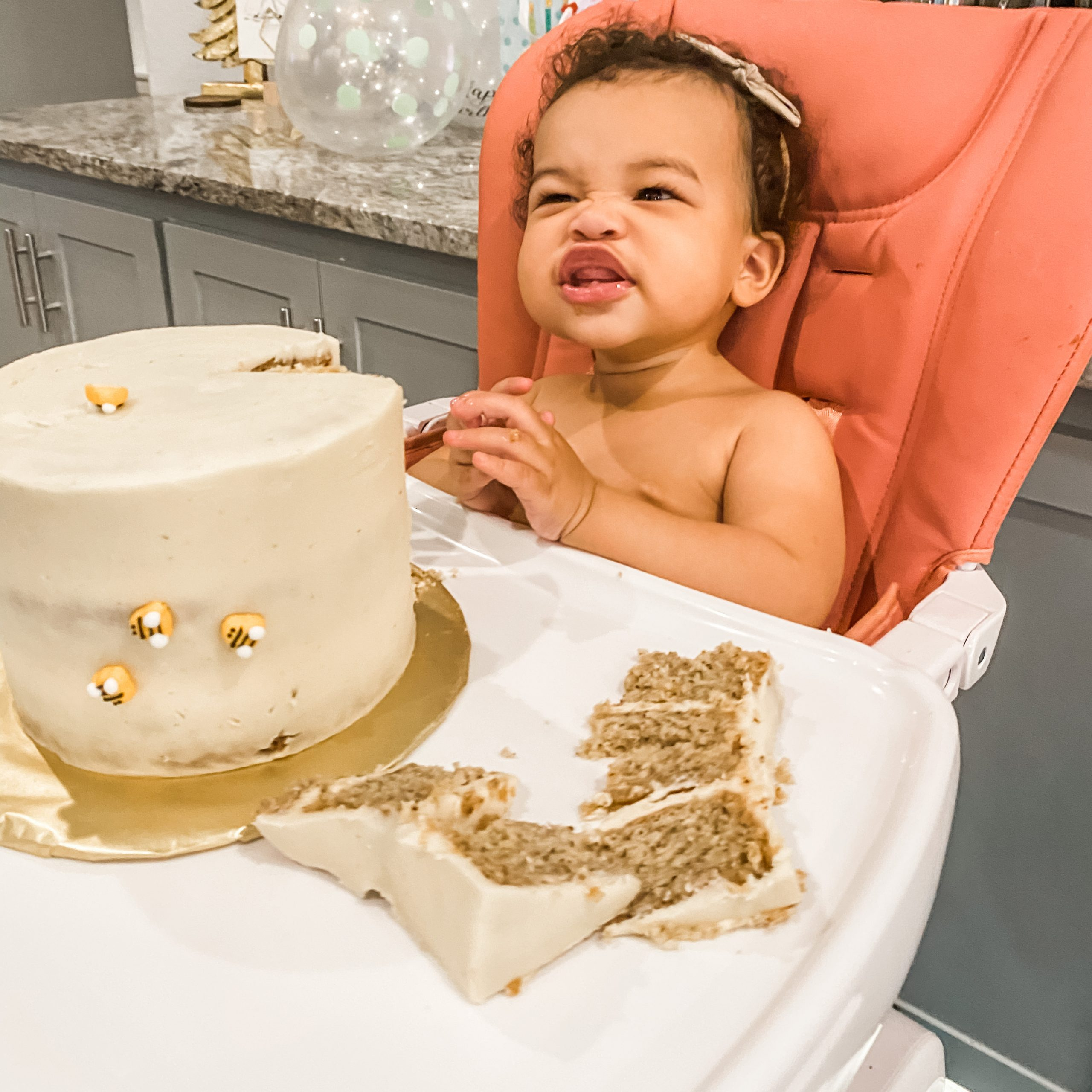 smiling baby with a smashed slice of cake