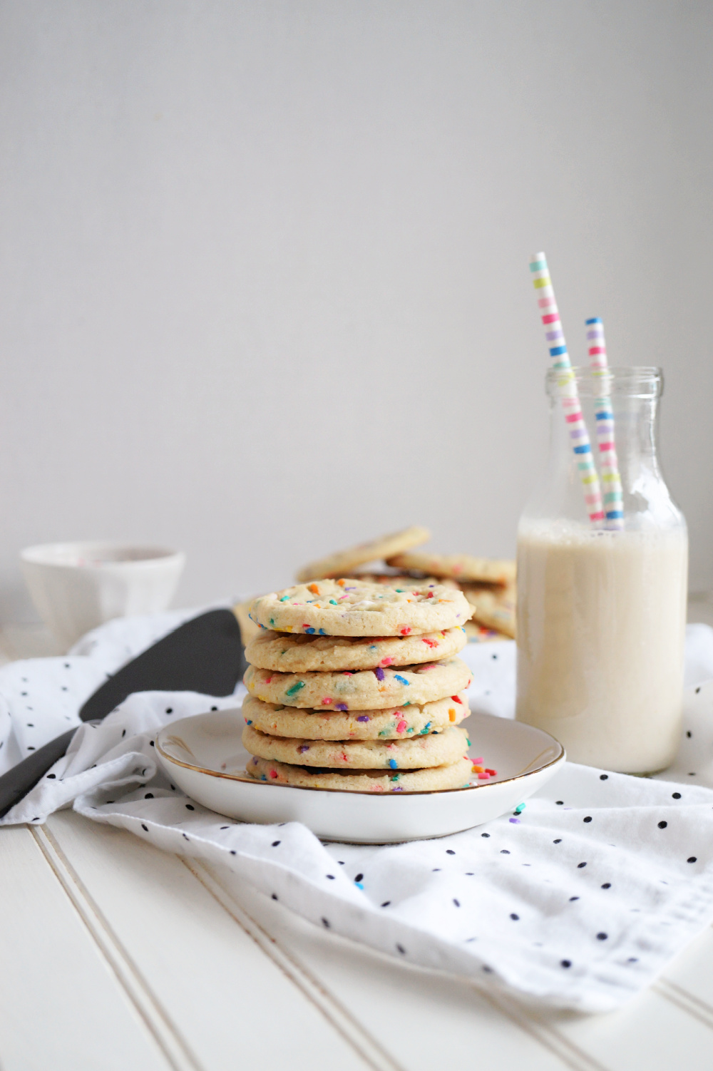 stack of confetti sugar cookies on plate with bottle of milk