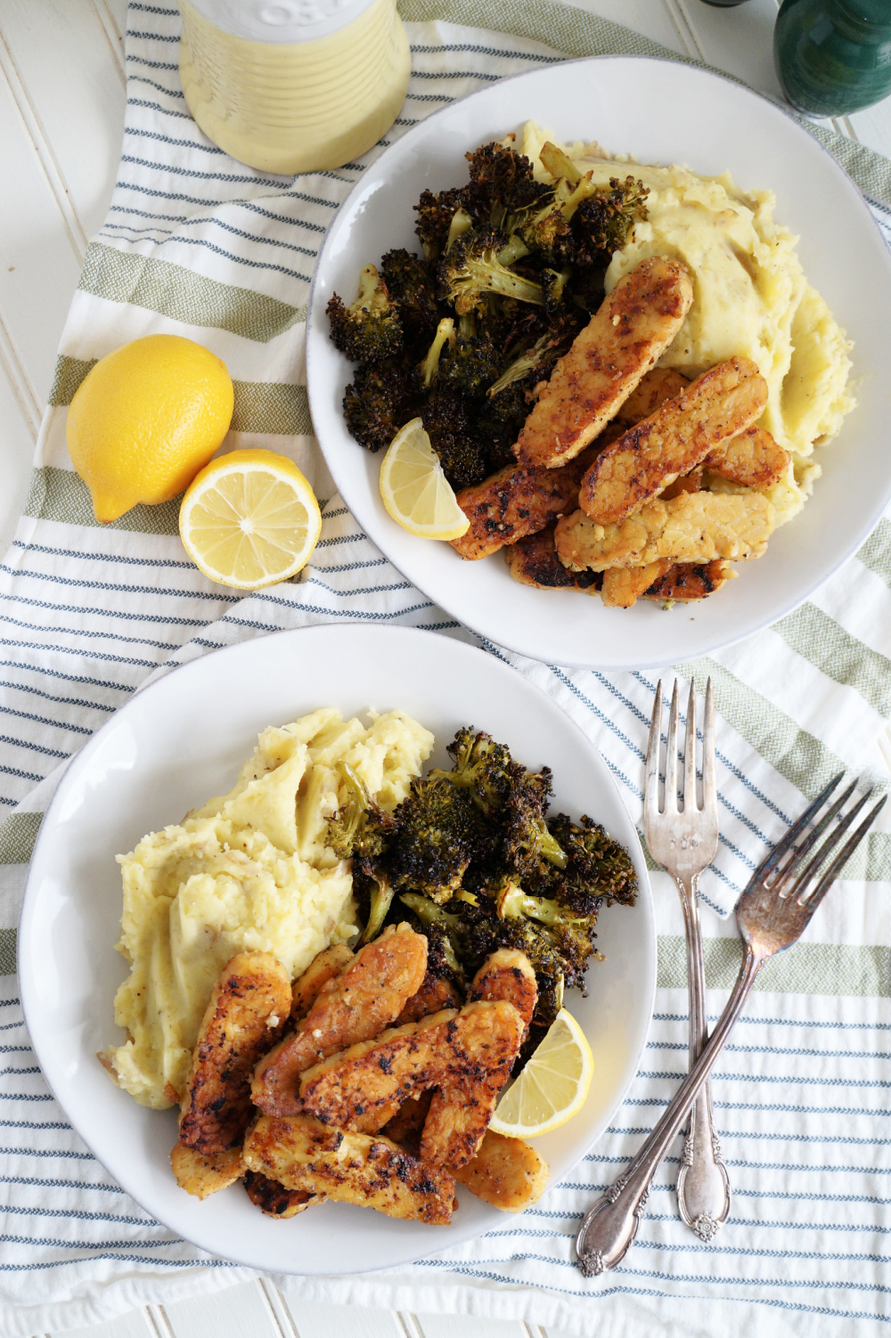 overhead shot of plates of lemon pepper tempeh with mashed potatoes and broccoli