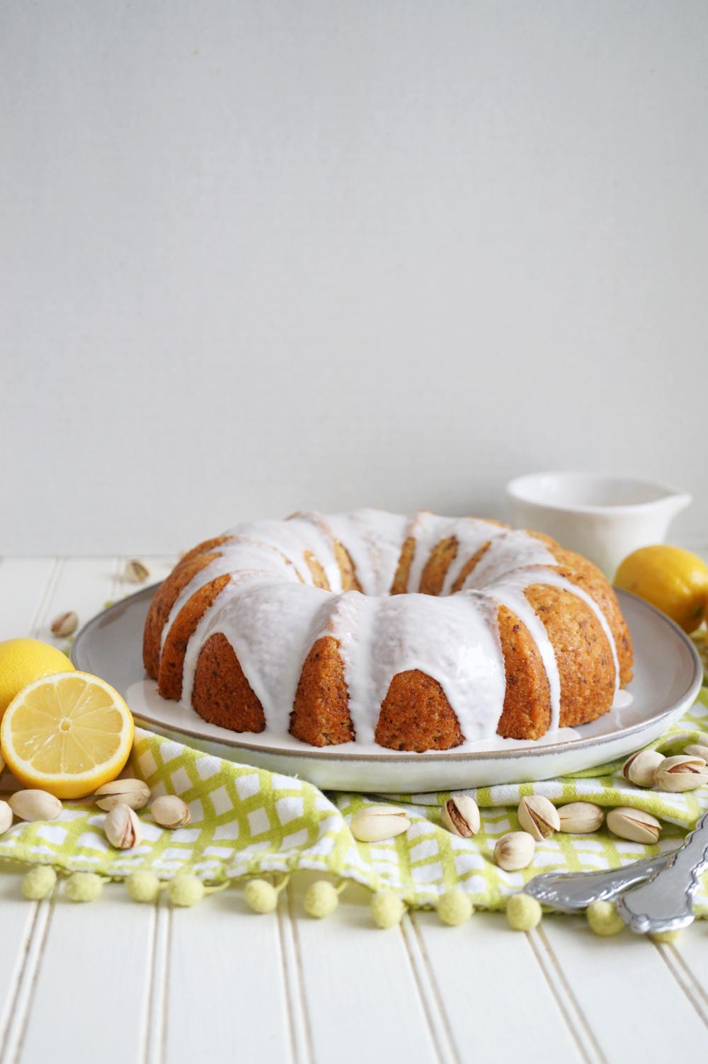 frosted lemon pistachio bundt cake on plate