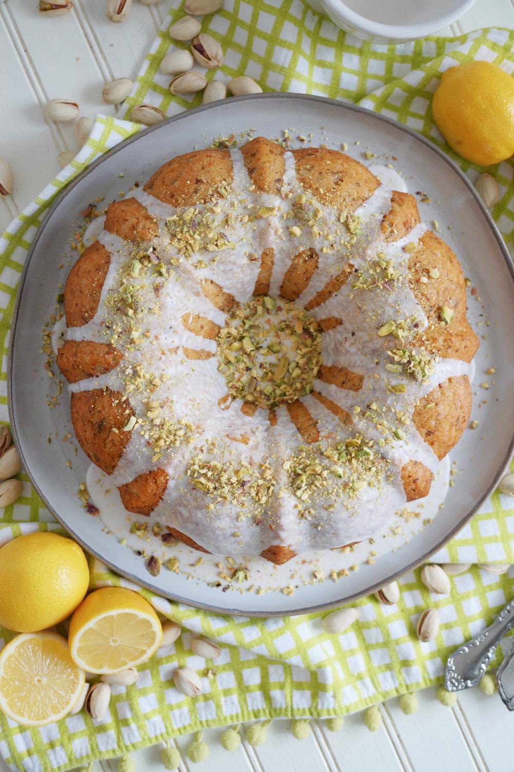 overhead photo of lemon pistachio bundt cake with glaze and pistachios on top