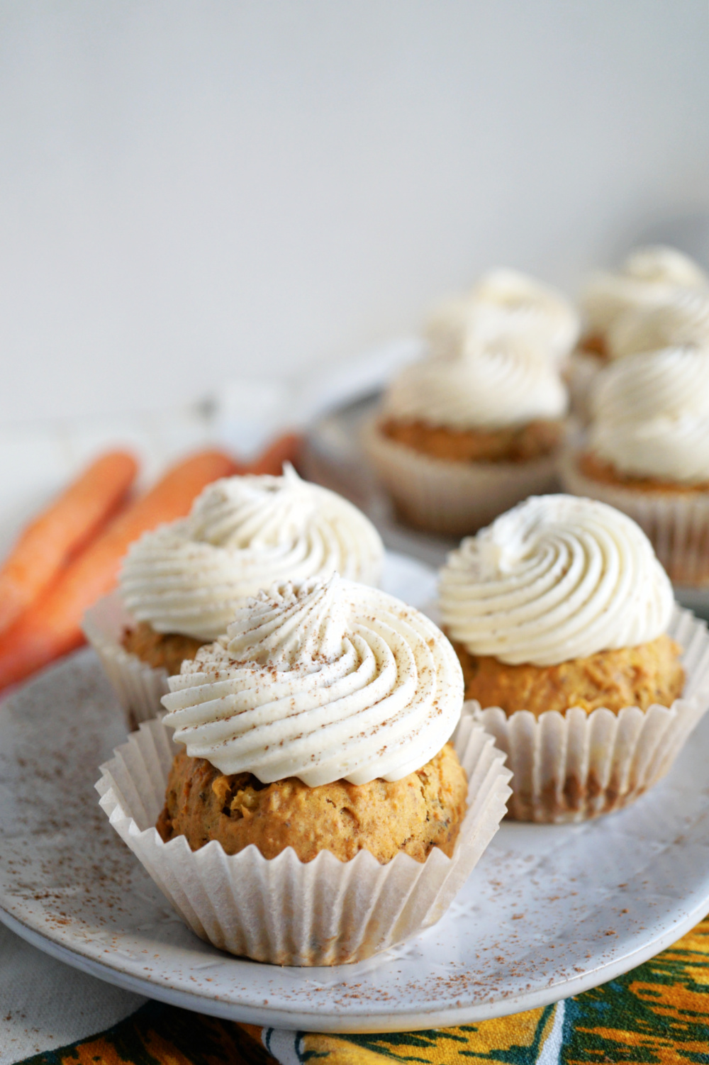 carrot cake cupcakes with white frosting on top