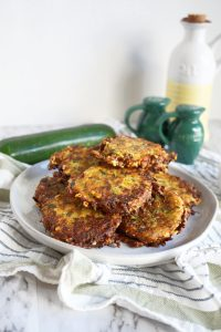 pile of golden brown cheesy zucchini fritters
