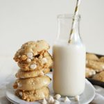 stack of white chocolate cookies next to bottle of milk