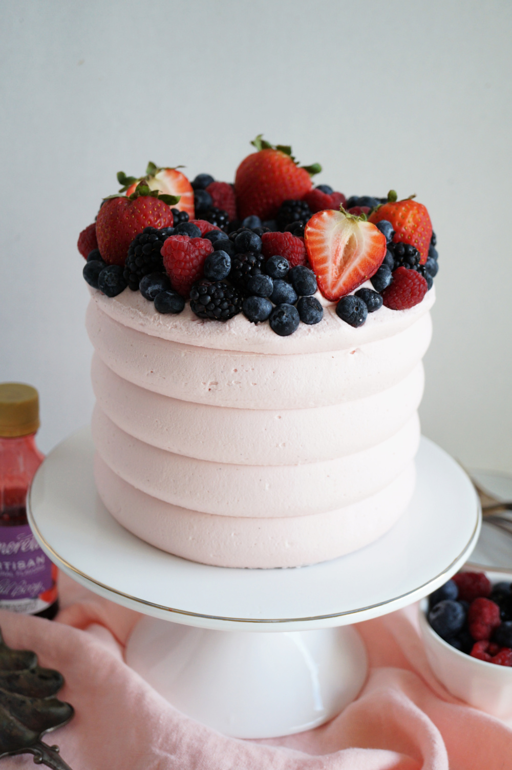 close up of berry cake on stand